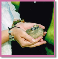 celebrant holding out rings on a blessed river rock for couple in spiritual wedding